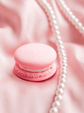 Girly, bakery and branding concept - Sweet macaroons and pearls jewellery on silk background, parisian chic jewelry, French dessert food and cake macaron for luxury confectionery brand, holiday gift Banque d'images