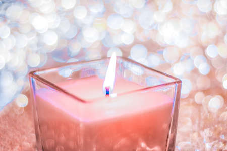 Festive decoration, branding and aromatherapy spa concept - Coral aromatic candle on Christmas and New Years glitter background, Valentines Day luxury home decor and holiday season brand design Stock Photo