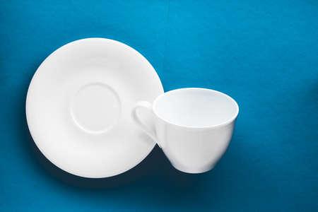 Concepto de menú de cocina, decoración de mesa y bebidas - juego de vajilla de vajilla blanca, taza vacía sobre fondo azul flatlay