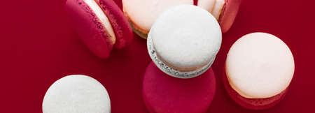 Pastry, bakery and branding concept - French macaroons on wine red background, parisian chic cafe dessert, sweet food and cake macaron for luxury confectionery brand, holiday backdrop design