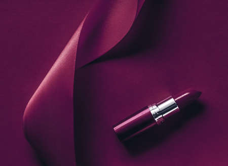 Cosmetic branding, glamour lip gloss and shopping sale concept - Luxury lipstick and silk ribbon on plum holiday background, make-up and cosmetics flatlay for beauty brand product design Stok Fotoğraf