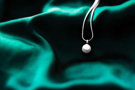 Jewellery brand, elegant fashion and bridal luxe gift concept - Luxury white gold pearl necklace on dark emerald green silk background, holiday glamour jewelery present Stock Photo