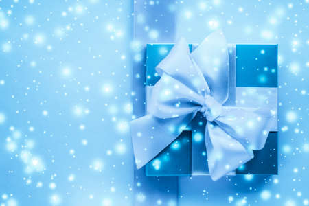 New Years Eve celebration, wrapped luxury boxes and cold season concept - Winter holiday gifts and glowing snow on frozen blue background, Christmas presents surprise Imagens