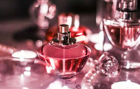 Perfumería, marca de cosméticos y concepto de lujo: frasco de perfume y fragancia vintage en el tocador de glamour por la noche, joyas de perlas y eau de parfum como regalo de vacaciones, presente de la marca de belleza de lujo