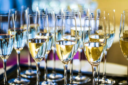 Drinks, celebration and luxury concept - Glasses of champagne and sparkling wine served on a tray during charity event Stock Photo