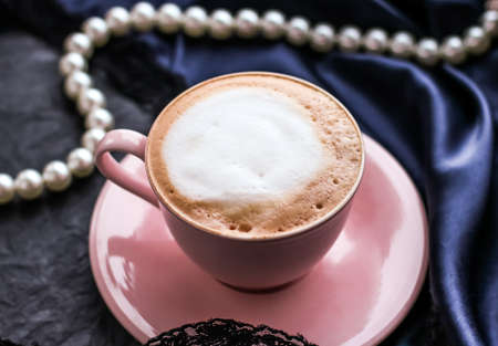 Cup of cappuccino and pearl jewellery on silk fabric, luxury cafe concept