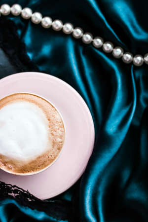 Cup of cappuccino and pearl jewellery on silk fabric, luxury cafe concept Stock fotó