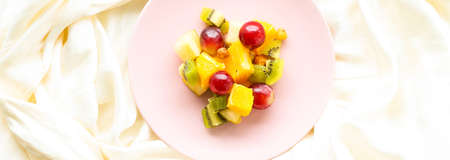 Fresh organic fruit salad on pink plate, healthy nutrition and detox diet plan, flat lay