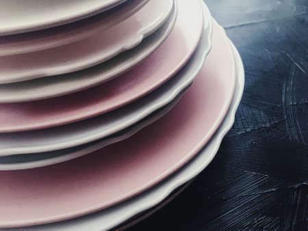 Stack of clean empty plates on black background, luxe dishware and table decor