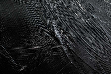 Dark gray background, charcoal paint texture as abstract backdrop, close-up