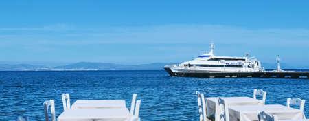 Kos Island, Greece circa May 2020: Empty restaurant by the Aegean sea and cruise boat