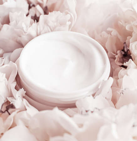 Luxe cosmetic cream jar as antiaging skincare routine product on background of peony flowers, body moisturizer and beauty branding design