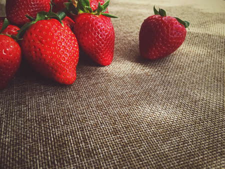 Organic strawberries on rustic linen background, fruit farming and agriculture