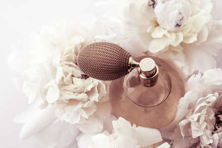 Retro fragrance bottle as luxury perfume product on background of peony flowers, parfum ad and beauty branding design
