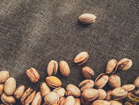 Pistachio nuts on rustic linen background, food and nutrition Фото со стока