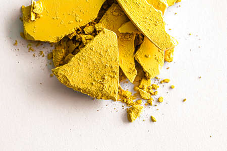 Yellow eye shadow powder as makeup palette closeup isolated on white background, crushed cosmetics and beauty textures