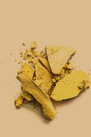 Yellow eye shadow powder as makeup palette closeup, crushed cosmetics and beauty textures