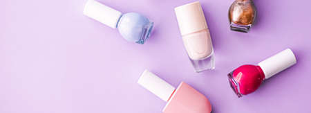 Nail polish bottles on purple background, beauty branding