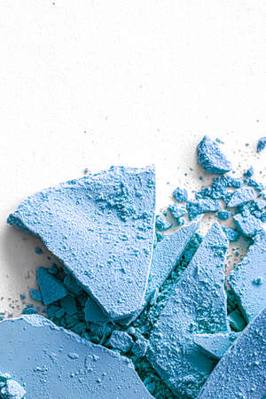 Blue eye shadow powder as makeup palette closeup isolated on white background, crushed cosmetics and beauty textures