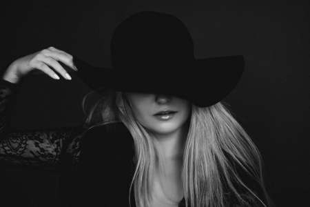 Beautiful blonde woman wearing a hat, artistic film portrait in black and white for fashion campaign and beauty brands Banco de Imagens