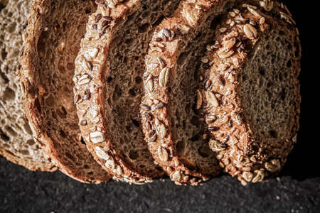 Fresh whole grain seeded bread, organic wheat flour, closeup slice texture as background for food blog or cook book recipes