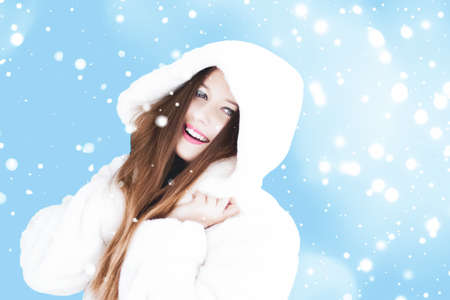 Christmas and winter holiday portrait of young woman in white hooded fur coat, snow on blue background, fashion and lifestyle campaign