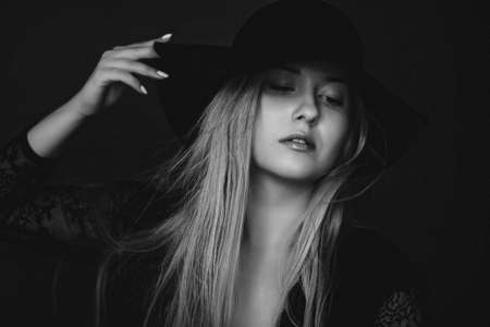 Beautiful blonde woman wearing a hat, artistic film portrait in black and white for fashion campaign and beauty brands 版權商用圖片
