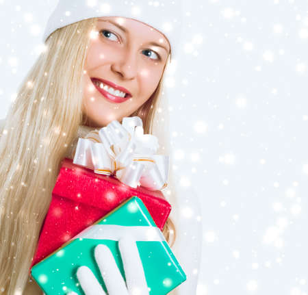 Happy woman holding Christmas gifts, silver background and snow glitter with copyspace, shopping and holidays
