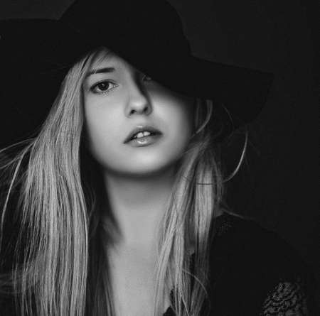 Beautiful blonde woman wearing a hat, artistic film portrait in black and white for fashion campaign and beauty brands Stok Fotoğraf
