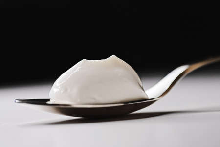 Thick white cream on golden spoon, closeup