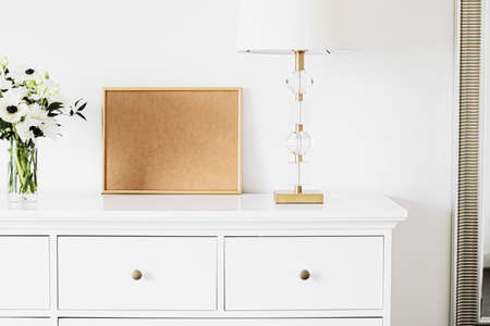 Golden horizontal frame and bouquet of fresh flowers on white furniture, luxury home decor and design for mockup creation