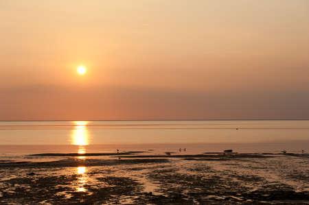 Ondergaande zon op het strand bij Ouddorp