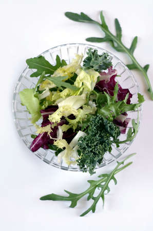 Bowl with lettuce leaves raw vegetarian salad