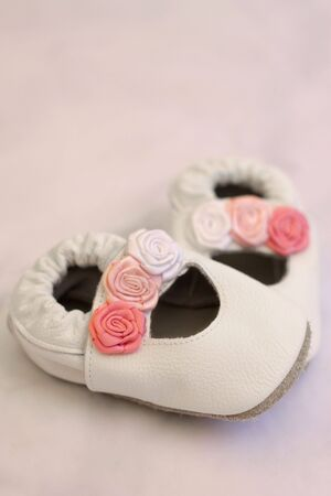 White leather shoes with roses for a small baby girl. Shot on grey background, soft focus Stock Photo
