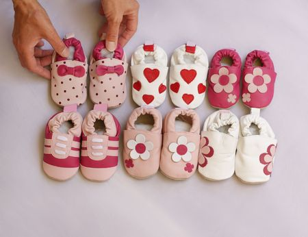 organising: Hands organising six pairs of baby shoes into two lines