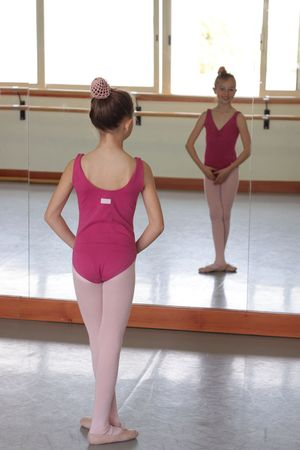 A young ballet girl smiling at the camera through the reflection of the dance studio mirror Stock Photo