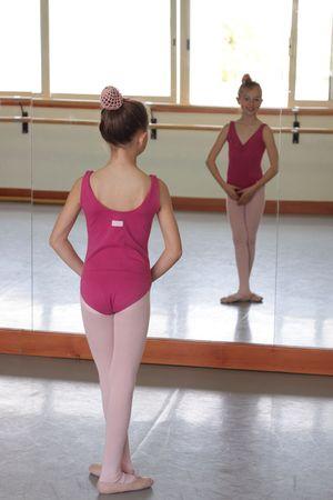 turnanzug: Ein Junge Ballett M�dchen l�chelnd in die Kamera durch die Reflexion von der Tanz-Studio-Spiegel  Lizenzfreie Bilder