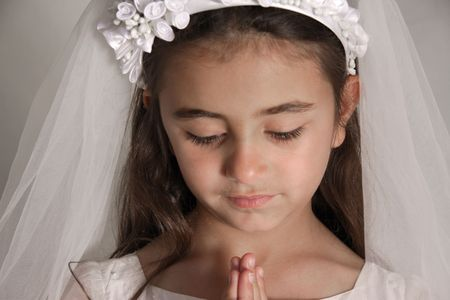 Girl in holy communion dress praying photo