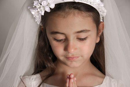 Girl in holy communion dress praying
