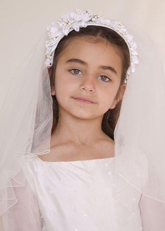 Portrait of a serious looking young girl who is celebrating her holy communion. The girl looks straight into the camera with big beautiful eyes. photo