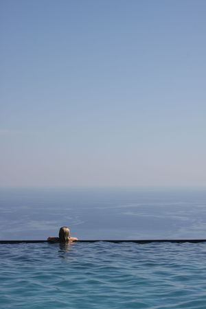Girl relaxing at the end of an infinity pool, looking at an amazing view of the Mediterranean Sea. Copy space to the right and above