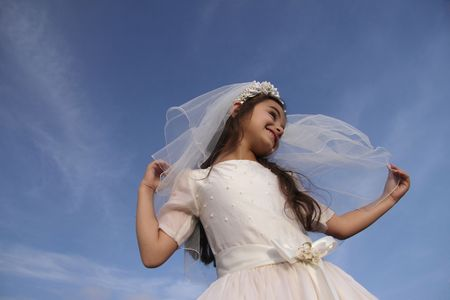 Girl in holy communion dress against blue sky, space for copy