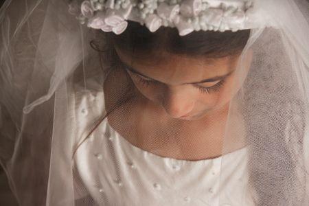ordenanza: Chica celebrando su primera comuni�n. Su rostro est� cubierto por su velo, y ella est� mirando hacia abajo. Sentimiento triste y grave. Foto horizontal  Foto de archivo