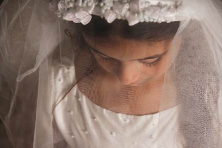 innocense: Girl celebrating her First Communion. Her face is covered by her veil, and she is looking down. Sad, serious feeling. Horizontal photo Stock Photo