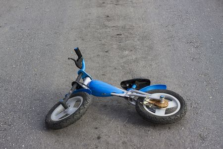An old kids push bike is abandoned in the middle of the road