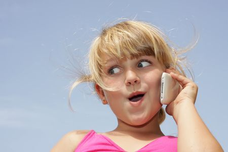 A young girl is doing a funny face while talking on her touch phone