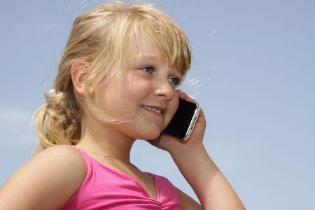 feeling positive: Una chica muy joven est� hablando sobre la �ltima versi�n de tel�fono de contacto, sentimiento positivo