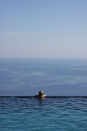 Girl looking at the endless sea view from an infinity pool photo