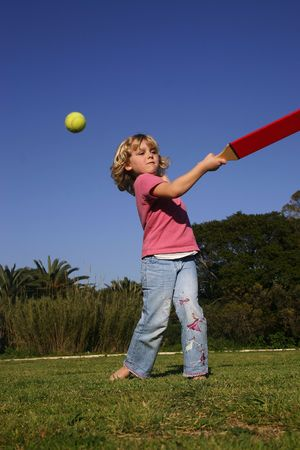 A young girl batting a ball, playing rounders (softball)