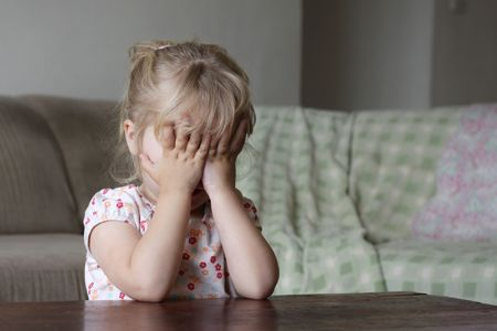 A toddler hiding her face behind her hands, could be scared, playing, counting, shy, or ashamed photo